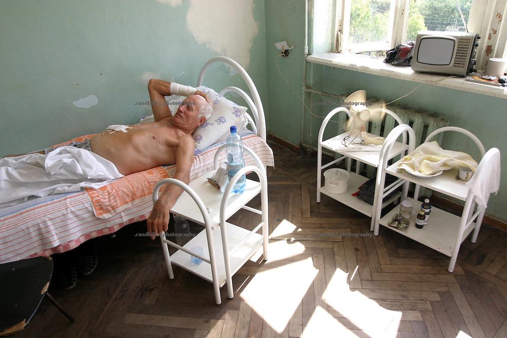 Georgien/Abchasien, Suchumi, 2006-08-27, Krankenzimmer mit gerade operierten Patienten im Republik-Krankenhaus von Suchumi. Abchasien erklärte sich 1992 unabhängig von Georgien. Nach einem einjährigen blutigen Krieg zwischen den Abchasen und Georgiern besteht seit 1994 ein brüchiger Waffenstillstand, der von einer UNO-Beobachtermission unter personeller Beteiligung Deutschlands überwacht wird. Trotzdem gibt es, vor allem im Kodorital immer wieder bewaffnete Auseinandersetzungen zwischen den Armee der Länder sowie irregulären Kämpfern. (Patient room with recently operated patients in the Republic-Hospital in Sukhumi. Abkhazia declared itself independent from Georgia in 1992. After a bloody civil war a UNO mission observing the ceasefire line between Georgia and Abkhazia since 1994. Nevertheless nearly every day armed incidents take place in the Kodori gorge between the both armys and unregular fighters )