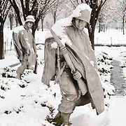 "Statues of the Korean War Veterans Memorial on the National Mall on a snowy winter morning. The Korean War Veterans Memorial, unveiled in 1992, sits on the northwestern end of the National Mall, not far from the Lincoln Memorial. It consists of several elements designed by different people and groups. It has a triangular footprint with the main elements being ""The Column"" consisting of 19 stainless steel solders, each over 7 feet tall, and a reflective granite wall etched with the faces of thousands of Americans who lost their lives in the war. At one end of the triangle, behind the soldiers, is a grove of trees. At the other is a large American flag and a small Pool of Remembrance. Among the designers were Frank Gaylord (the soldiers) and Louis Nelson (the reflecting granite wall)."