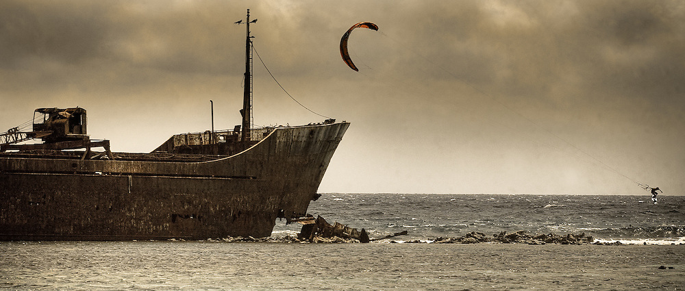 Pro kiteboarder Alvaro Onieva jumps in front of a large shipwrecked ship