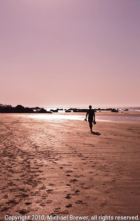Sihlouette of man walking along a sunset beach