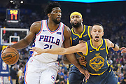 January 31, 2019; Oakland, CA, USA; Philadelphia 76ers center Joel Embiid (21) dribbles the basketball against Golden State Warriors center DeMarcus Cousins (0) and guard Stephen Curry (30) during the first quarter at Oracle Arena.