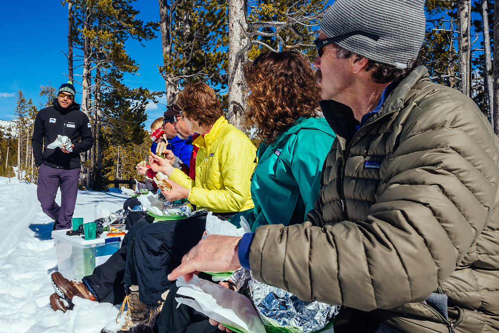 Clients eat lunch near Canyon in winter in Yellowstone National Park.