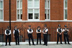 © Licensed to London News Pictures. 19/08/2012. Police waiting nearby the entrance to the Ecuador Embassy before  Wikileaks founder Julian Assange gives a speech from a balcony at The Ecuador Embassy in London on August 19/08/2012. Assange, who faces arrest by British police if he leaves the building, took refuge in the embassy on June 19 to evade extradition to Sweden where he is wanted for questioning over alleged sexual misconduct. Photo credit : Ben Cawthra/LNP