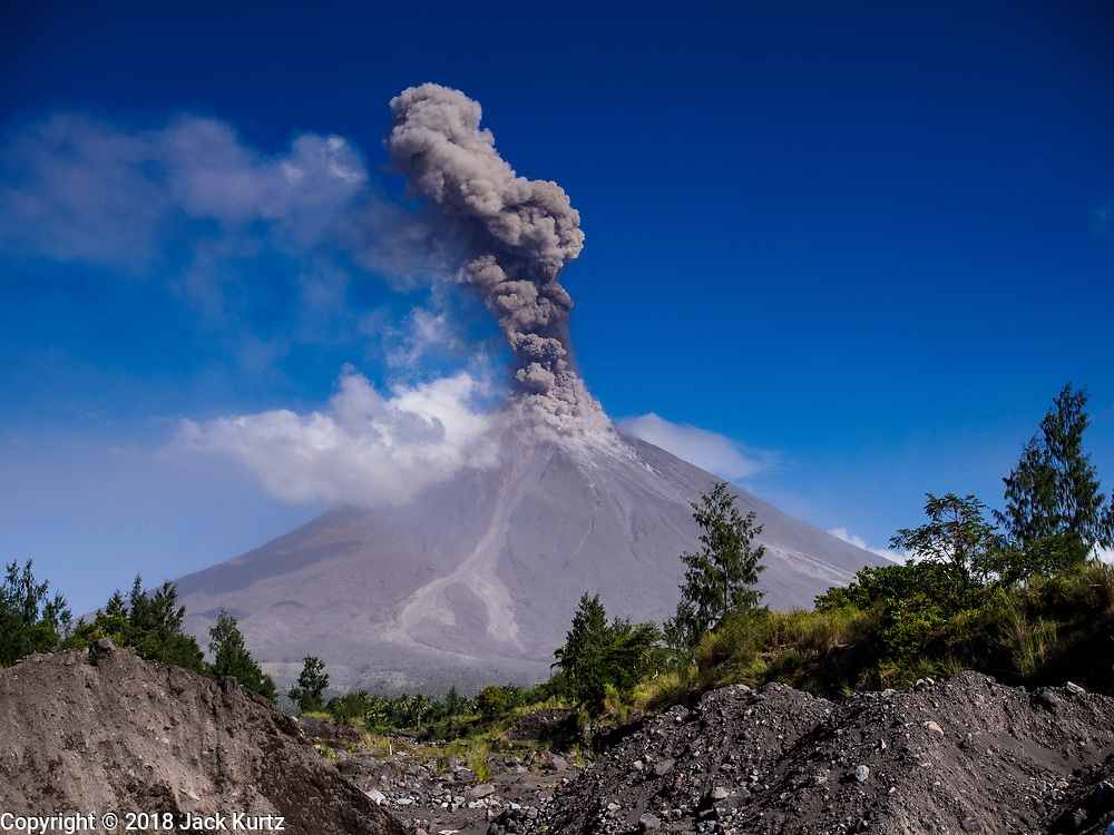 23 JANUARY 2018 - DARAGA, ALBAY, PHILIPPINES: The Mayon volcano erupts Tuesday morning. The Mayon volcano continued to erupt Tuesday, although it was not as active as it was Monday. There were ash falls in communities near the volcano. This is the most active the volcano has been since 2009. Schools in the vicinity of the volcano have been closed and people living in areas affected by ash falls are encouraged to stay indoors, wear a mask and not participate in strenuous activities.    PHOTO BY JACK KURTZ