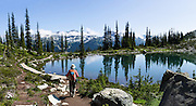 Harmony Lake reflects trees and blue sky along the High Note Trail on Whistler Mountain, in the Coast Range, British Columbia, Canada. See Blackcomb Mountain (2440 meters) and ski area in the Spearhead Range across Fitzsimmons Valley. The Resort Municipality of Whistler is popular for year-round outdoor sports. This panorama was stitched from 4 overlapping photos.