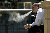 OAKLAND  CA. APRIL 25: A man smokes a cigar on April 25, 2005 in Oakland California  Photo by David Paul Morris