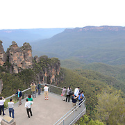 Tourists stand on one of the viewing platfooms at Echo Point in the Blue Mountains overlooking the rock formation known as the Three Sisters. Katoomba, New South Wales, Australia.