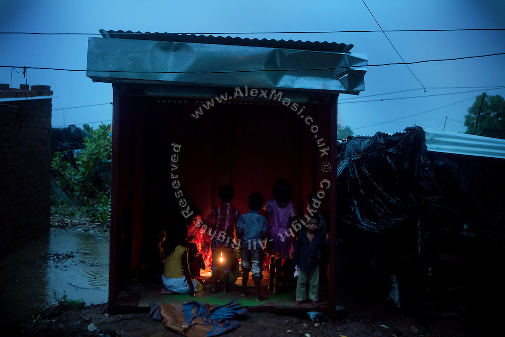 A .Puja. (worship) for good auspices is taking place inside a newly opened tailor shop in the impoverished Oriya Basti colony, Bhopal, Madhya Pradesh, India, near the abandoned Union Carbide (now DOW Chemical) industrial complex. Copyright: Alex Masi / Focus For Humanity