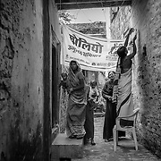 Community mobilizers put up a banner of the polio campaign across a narrow lane at a muslim area on the outskirts of Patna, Bihar
