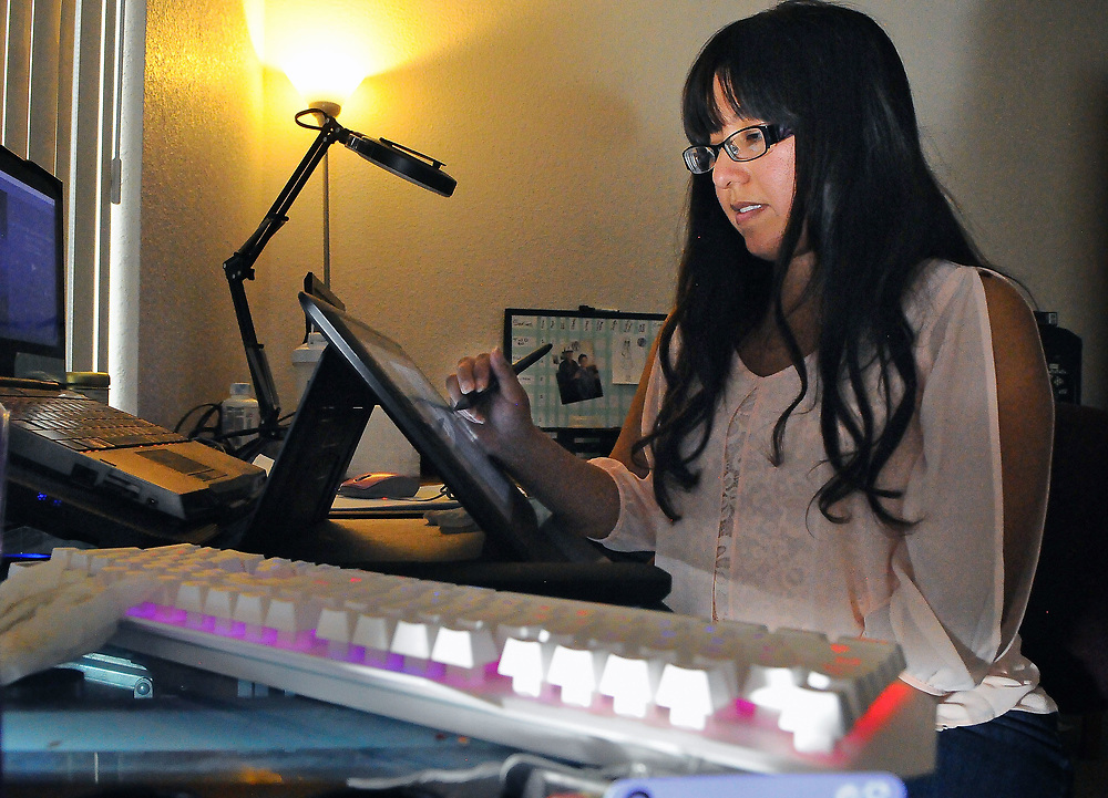 jt072017f/ spec sec/jim thompson/ Isabel Lucero draws on her tablet creating digital art for her graphic novels that she and her husband Mario produce for their website, Heaven Sent Gaming.Thursday,  July. 20, 2017. (Jim Thompson/Albuquerque Journal)