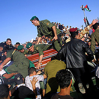 Palestinian soldiers escort the coffin of the late Palestinian leader Yassar Arafat, as mourners surge the Mukata compound in Ramallah in attempts to touch the coffin before the burial.  Friday Nov. 12, 2004.  To the roars of tens of thousands of Palestinians, and shots in the air fired by tense Palestinian police and masked gunmen, the flag-draped casket of Yasser Arafat was borne through milling, surging crowds Friday for burial in a plot next to the office to which Israel confined the Palestinian leader for nearly three years.  Photo by Olivier Fitoussi.. ..