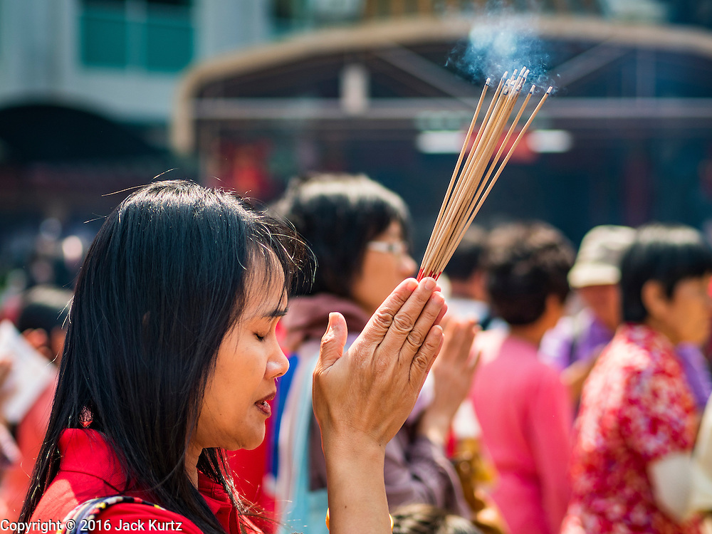 "08 FEBRUARY 2016 - BANGKOK, THAILAND: A woman prays during Chinese New Year observances at Kuan Yim Shrine in Bangkok's Chinatown district, during the celebration of the Lunar New Year. Chinese New Year is also called Lunar New Year or Tet (in Vietnamese communities). This year is the ""Year of the Monkey."" Thailand has the largest overseas Chinese population in the world; about 14 percent of Thais are of Chinese ancestry and some Chinese holidays, especially Chinese New Year, are widely celebrated in Thailand.       PHOTO BY JACK KURTZ"