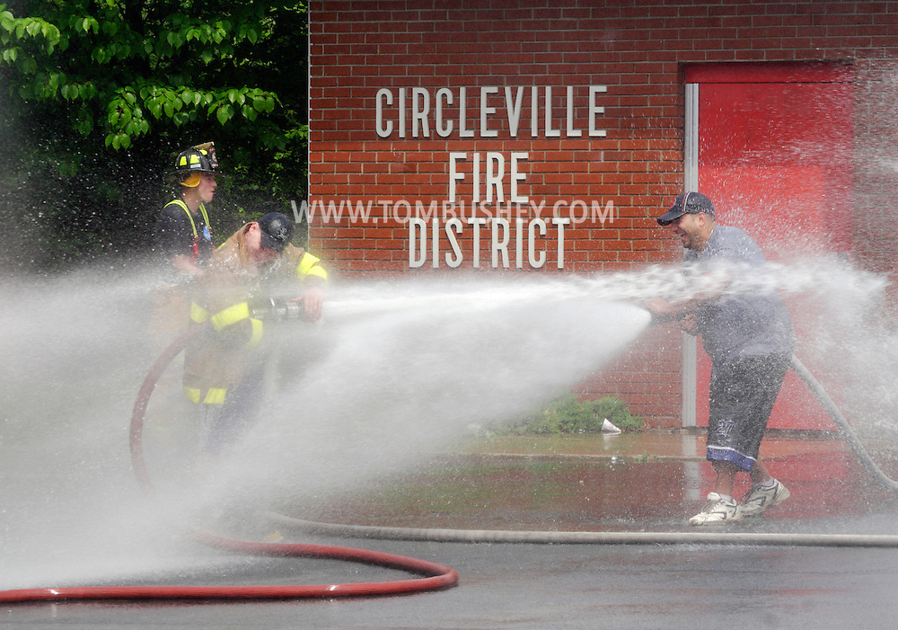 Circleville, NY - Firefighters spray water at each other during the ceremonial wetdown of a new fire trick at the Circleville Firehouse on May 31, 2008.