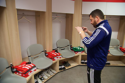 HAIFA, ISRAEL - Saturday, March 28, 2015: Wales' equipment manager David Griffiths takes a photo of the shirts and boots for Wales players laid out in the dressing room ahead of the UEFA Euro 2016 qualifying Group B match against Israel at the Sammy Ofer Stadium. (Pic by David Rawcliffe/Propaganda)