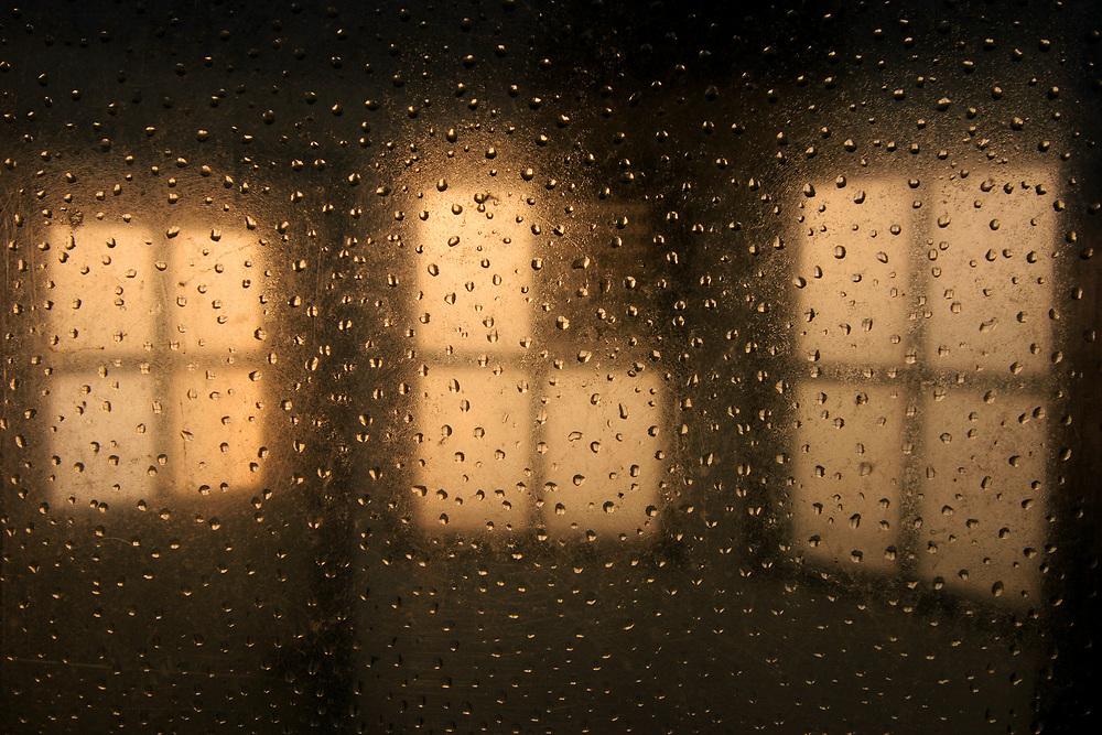 Dops of water on the window of an old lighthouse in Oostmahorn at sunrise // Druppels condens op een raam van het oude vuurtorentje van Oostmahorn aan het Lauwersmeer tijdens zonsopkomst.