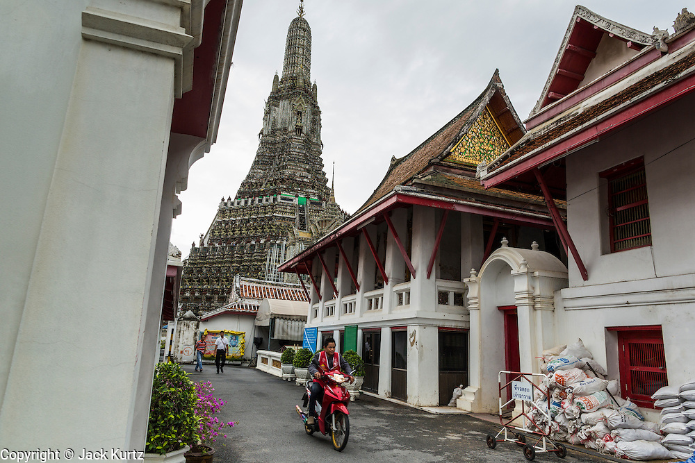 "23 SEPTEMBER 2013 - BANGKOK, THAILAND: A motorcycle taxi drives out of Wat Arun in Bangkok. The famous central prang of the temple is in the background. The full name of the temple is Wat Arunratchawararam Ratchaworamahavihara. The outstanding feature of Wat Arun is its central prang (Khmer-style tower). The world-famous stupa, known locally as Phra Prang Wat Arun, will be closed for three years to undergo repairs and renovation along with other structures in the temple compound. This will be the biggest repair and renovation work on the stupa in the last 14 years. In the past, even while large-scale work was being done, the stupa used to remain open to tourists. It may be named ""Temple of the Dawn"" because the first light of morning reflects off the surface of the temple with a pearly iridescence. The height is reported by different sources as between 66,80 meters and 86 meters. The corners are marked by 4 smaller satellite prangs. The temple was built in the days of Thailand's ancient capital of Ayutthaya and originally known as Wat Makok (The Olive Temple). King Rama IV gave the temple the present name Wat Arunratchawararam. Wat Arun officially ordained its first westerner, an American, in 2005. The central prang symbolizes Mount Meru of the Indian cosmology. The temple's distinctive silhouette is the logo of the Tourism Authority of Thailand.           PHOTO BY JACK KURTZ"