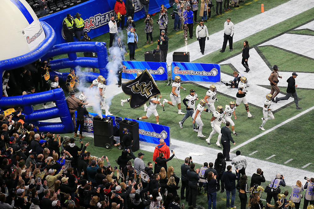 The UCF Knights run out of the tunnel prior to the NCAA football game on Monday, January 1, 2018 in Atlanta. (Daniel Shirey / Abell Images for the Chick-fil-A Peach Bowl)