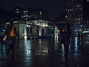 Pedestrians walk past the pavillion in the north plaza of Union Square on a rainy winter night.