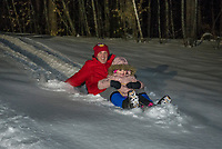 Jeff and Alexis Dionne take a ride through the fresh snow during Laconia Parks and Rec's Sledding Party  at Memorial Hill on Friday evening.  (Karen Bobotas/for the Laconia Daily Sun)