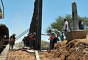 Workers replace a 2.8 mile section of landing matt border wall constructed in 1994 in Nogales, Arizona, USA, at Sonora, Mexico.  The project costs $11.6 million.  Under tight security on the Arizona side of the border, the construction draws much interest from residents of Nogales, Sonora, Mexico.  The concrete marker originally designated the border.