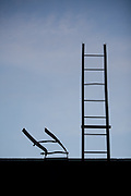 Two ladders, one short and crooked and one tall and straight rise up into the sky.