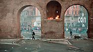 Roma  15 Ottobre 2011.Manifestazione contro la crisi e l'austerità.Scontri tra manifestanti e forze dell'ordine.Manifestanti fronteggiano le forze dell'ordine in piazza San Giovanni  tra il fumo dei lacrimogeni, un incendio sulle mura