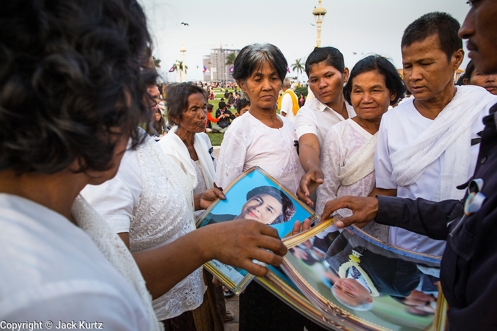 "30 JANUARY 2013 - PHNOM PENH, CAMBODIA: Cambodian women wearing white mourning buy photos of late Cambodian King Norodom Sihanouk in Phnom Penh. Sihanouk (31 October 1922 - 15 October 2012) was the King of Cambodia from 1941 to 1955 and again from 1993 to 2004. He was the effective ruler of Cambodia from 1953 to 1970. After his second abdication in 2004, he was given the honorific of ""The King-Father of Cambodia."" Sihanouk held so many positions since 1941 that the Guinness Book of World Records identifies him as the politician who has served the world's greatest variety of political offices. These included two terms as king, two as sovereign prince, one as president, two as prime minister, as well as numerous positions as leader of various governments-in-exile. He served as puppet head of state for the Khmer Rouge government in 1975-1976. Most of these positions were only honorific, including the last position as constitutional king of Cambodia. Sihanouk's actual period of effective rule over Cambodia was from 9 November 1953, when Cambodia gained its independence from France, until 18 March 1970, when General Lon Nol and the National Assembly deposed him. Upon his final abdication, the Cambodian throne council appointed Norodom Sihamoni, one of Sihanouk's sons, as the new king. Sihanouk died in Beijing, China, where he was receiving medical care, on Oct. 15, 2012. His cremation is scheduled to take place on Feb. 4, 2013. Over a million people are expected to attend the service.        PHOTO BY JACK KURTZ"