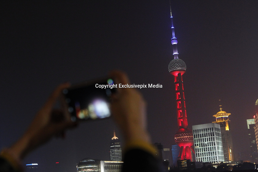 SHANGHAI, CHINA - NOVEMBER 14: (CHINA OUT) <br /> <br /> A citizen takes photos of the Oriental Pearl Tower being lighted up in red, white and blue colors of French national flag to mourn the victims in French terror attack on November 14, 2015 in Shanghai, China. French suffered savage terror attach Friday night at Stade de France and a central restaurant as well as several other places which caused at least 128 dead, with 250 people wounded, 99 in critical situation, said local media. <br /> ©Exclusivepix Media