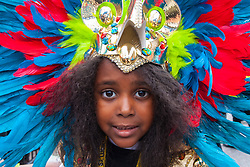 London, August 24th 2014. A little girl's vibrant head dress contributes to the colour as revellers participate in 2014's Notting Hill Carnival in London, celebrating West Indian and other cultures, attracting hundreds of thousands to Europe's biggest street party.