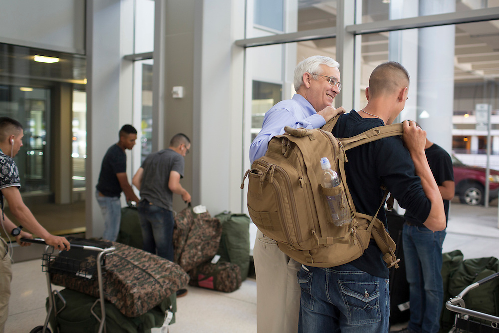 """John Falkenbury, 59, President of the North Carolina USO, greets Marines on their way to Camp Lejeune at Raleigh-Durham International Airport on Wednesday, July 15, 2015. This fall, AARP-North Carolina plans workshops for veterans on issues ranging from saving for retirement, family caregiving, financial literacy, job resources and planning the next steps in their life and career with """"Life Reimagined."""""""