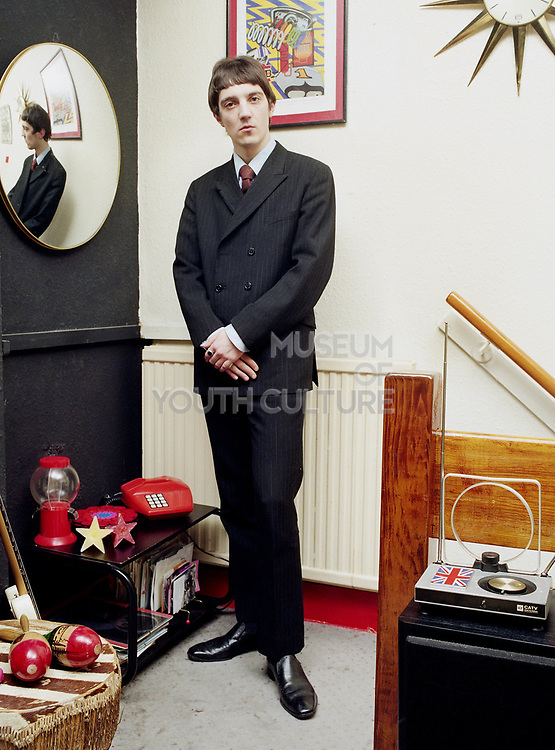 Young man wearing a Mod style suit standing in a retro designed room.