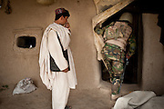 An Afghan boy watches as an Afghan National Army soldier enters his home to search it.