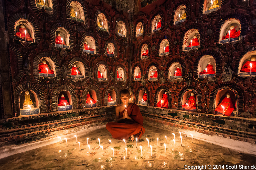 A young novice monk meditiates in a temple in Myanmar.