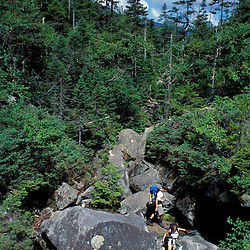 Hiking Mahoosuc Notch Trail, possibly the hardest mile of the Appalachian Trail due to a maze of giant boulders.  Mahoosuc Range, White Mountains.  Mahoosuc Notch, ME