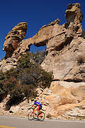 Cyclists make their way past a natural arch on Mount Lemmon, Santa Catalina Mountains, Coronado National Forest, Sonoran Desert, Tucson, Arizona, USA.
