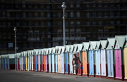 © Licensed to London News Pictures. 03/07/2018. Hove, UK. A man walks past colourful beach huts on the seafront at Hove, East Sussex on the south coast of England, as a heatwave continues across the UK. Photo credit: Ben Cawthra/LNP