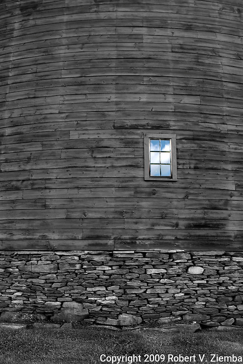A black and white image of a section of a round barn on a stone foundation with one window colored blue