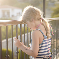 Female youth outdoors on balcony holding railing looking down at street