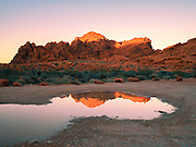 Red rock formations near Mouse's Tank Trail, Valley of Fire State Park, Nevada reflected in a puddle shortly before sunset. Light from the sun catches the red sandstone in its glow.  Valley of Fire State Park is located in the Mojave Desert in southern Nevada.