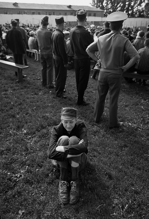 A prisoner seats on the grass during colony's school graduation at the colony for prisoner's children in Siberian town Leninsk-Kuznetsky, Russia, 15 June 2001.