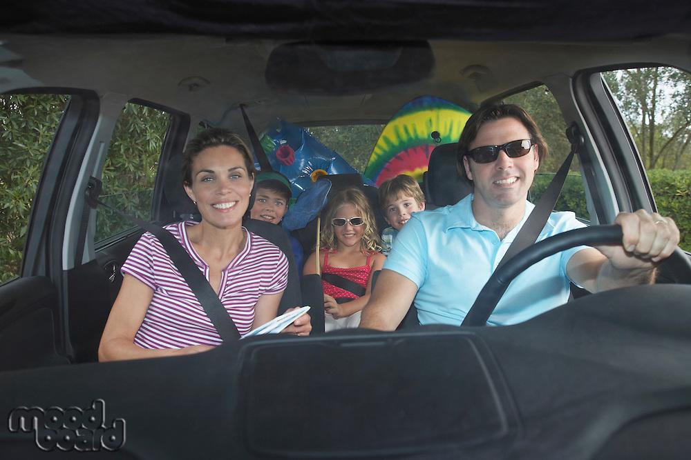 Family with three children (5-11) in car interior portrait