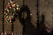 """The shadows of veterans who are providing night security for the Traveling Vietnam Veterans Memorial, the """"Traveling Wall"""",  and a wreath are cast onto the face of the memorial wall during its visit to Petoskey, Michigan."""
