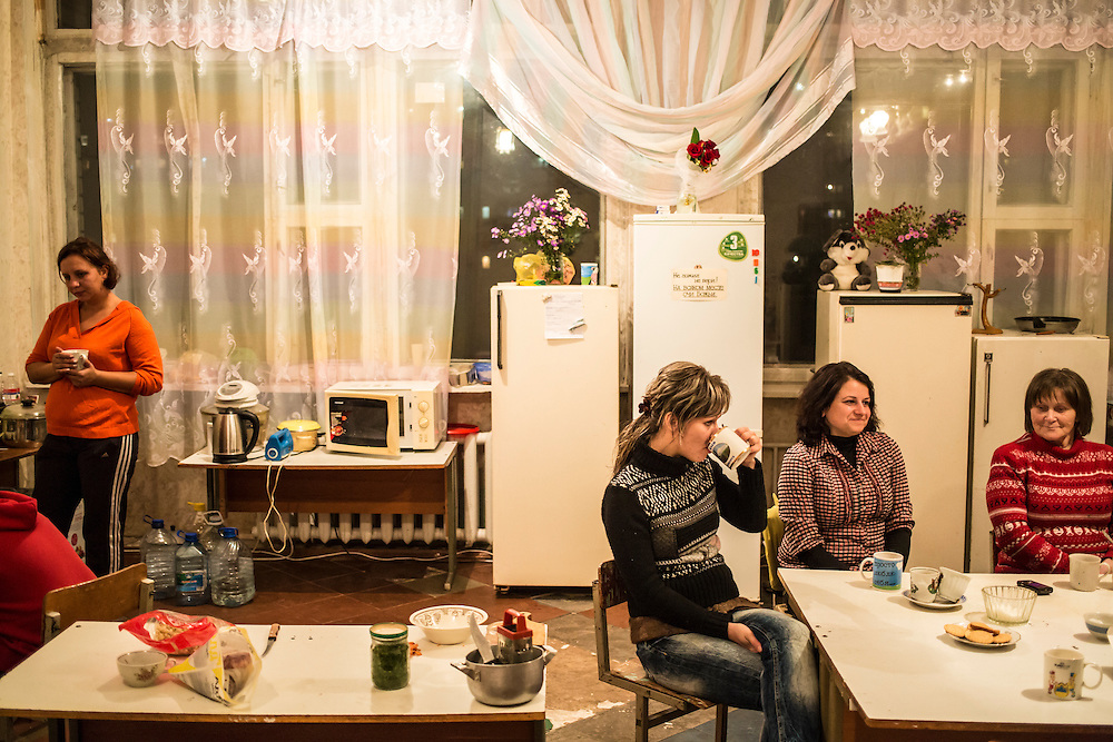 DNIPRODZERZHINSK, UKRAINE - OCTOBER 11: Women share tea while another woman prepares dinner for her family in the communal kitchen in the sports school where about 60 people displaced by fighting in Eastern Ukraine live on October 11, 2014 in Dniprodzerzhinsk, Ukraine. The United Nations has registered more than 360,000 people who have been forced to leave their homes due to fighting in the East, though the true number is believed to be much higher.(Photo by Brendan Hoffman/Getty Images) *** Local Caption *** ***