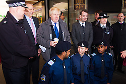 Ealing, London, December 9th 2014. Mayor of London Boris Johnson visits Ealing accompanied by Met Police Commissioner Sir Bernard Hogan-Howe hold a walkabout in Ealing to announce details of the historic deal secured for the New Scotland Yard site in Victoria. PICTURED: Boris Johnson poses for a picture with volunteer police cadets in Ealing Broadway shopping centre.