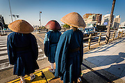 Three men in traditional clothing prepare to cross the street in Kyoto, Japan