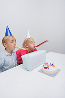 Siblings blowing noisemakers at birthday party in house