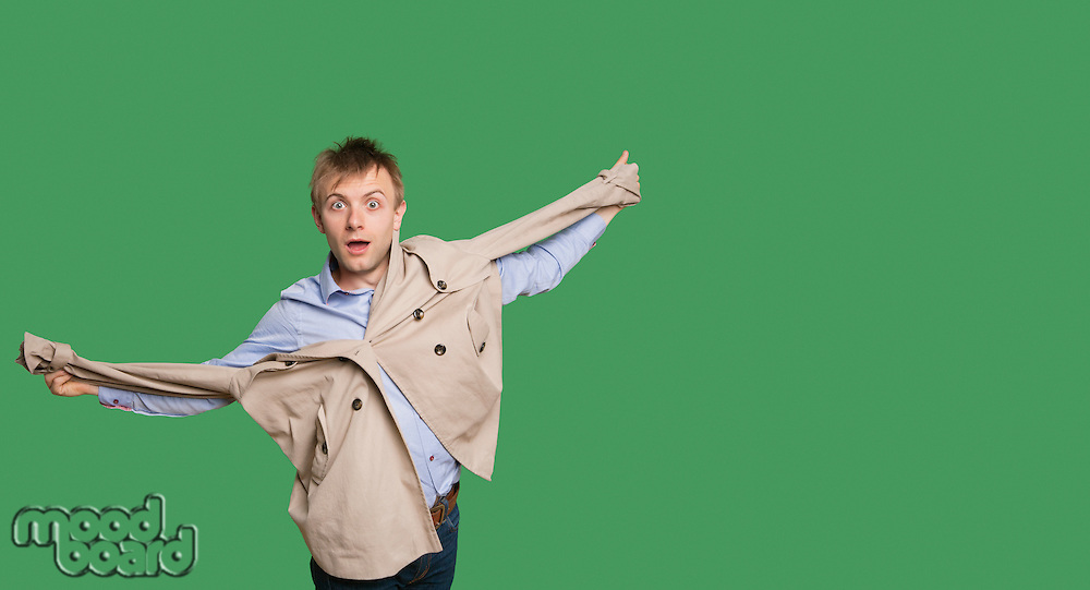 Portrait of amazed young man with jacket over colored background