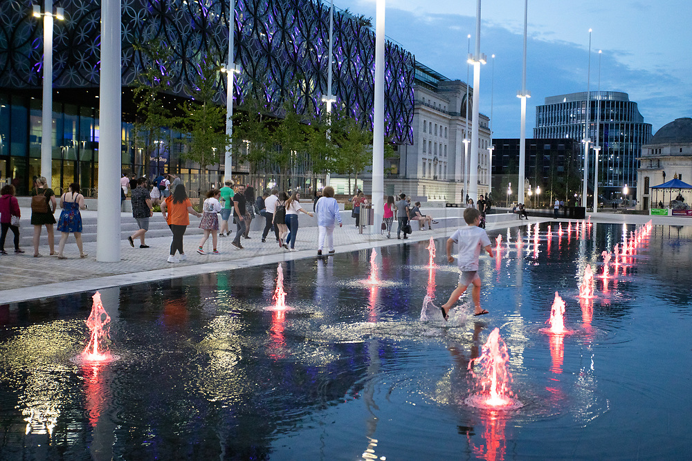 """© Licensed to London News Pictures. 05/07/2019. Birmingham, West Midlands UK. The hoardings were removed this week on the first phase of the £16m development of Centenary Square, Birmingham. A mirror lake was revealed with coloured fountains rising and falling in sporadic sequences. Already, only days after opening it has caused a Brummie """"Walking on Water"""" craze as toddlers, children, cyclists, shoppers and City staff have taken to walking between the fountains on their way to the New Library of Birmingham and the ICC. Photo credit: Dave Warren/LNP"""
