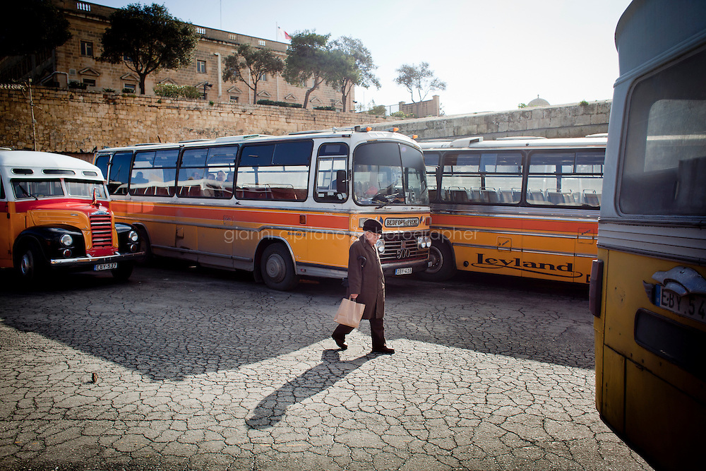 25 February 2011. Valletta, Malta. A man walks by parked Maltese buses at the bus terminal at the City Gate in Valletta, Malta. These buses, some of which are 60 years old, will be replaced in the following months by newer buses. There are approximately 500 buses in public transit service in Malta. The drivers themselves own most of the buses, but operate to a unified timetable set by the transport authority.<br /> <br /> <br /> &copy;2011 Gianni Cipriano<br /> cell. +1 646 465 2168 (USA)<br /> cell. +39 328 567 7923<br /> gianni@giannicipriano.com<br /> www.giannicipriano.com