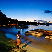 A local girl standing on the beach of Cruz Bay watching the sunset over the harbor